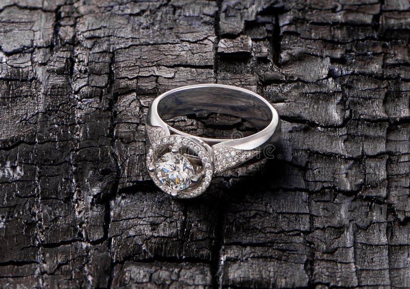 Anel de diamante no fundo queimado imagem de stock