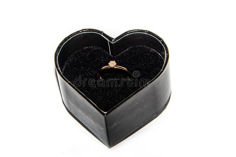 Anel de noivado brilhante bonito com o diamante na caixa de veludo da forma do coração isolada no dia de Valentim branco do fundo fotografia de stock royalty free