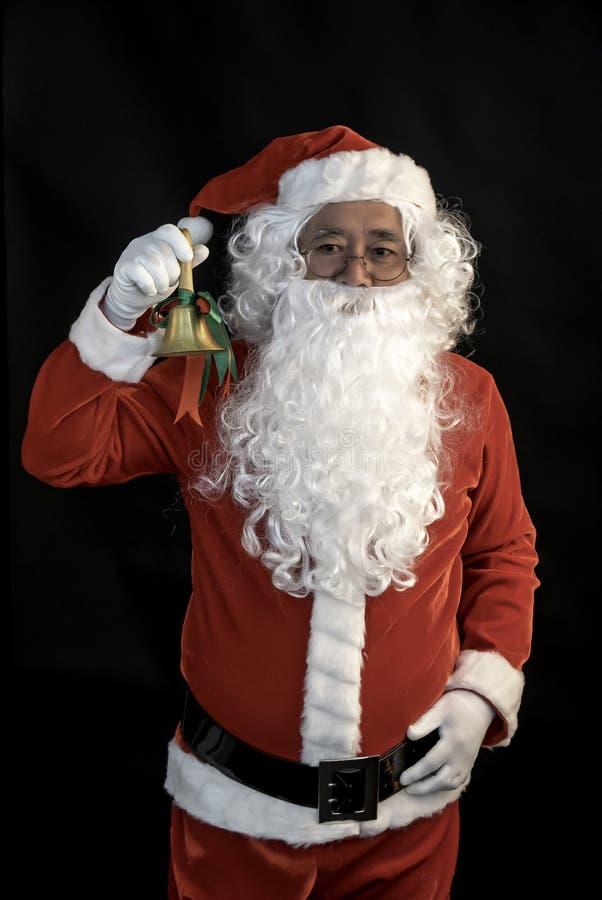 Anel de Santa Claus um sino em seu estúdio da mão do elevador disparado no fundo preto para a família, dando, estação, Natal, fer fotos de stock royalty free