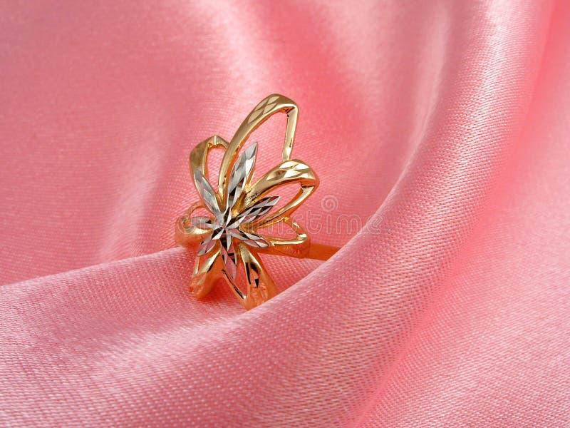 Anel dourado em dobras de seda rosados imagem de stock