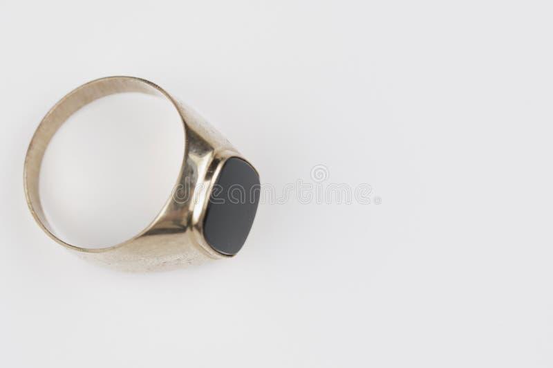 Anel dourado masculino com pedra preta em um fundo branco foto de stock royalty free