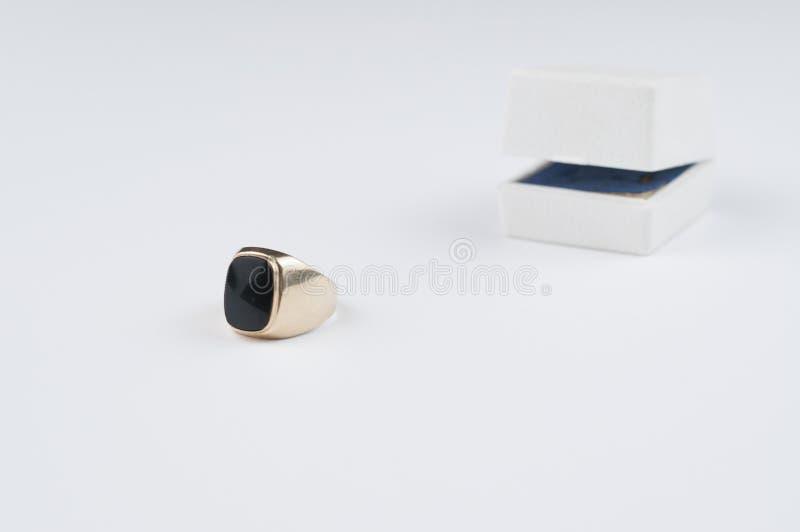 Anel dourado masculino com pedra preta em um fundo branco fotos de stock
