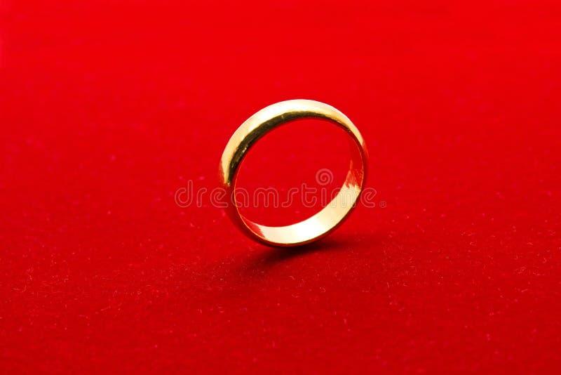Anel dourado no fundo vermelho fotografia de stock