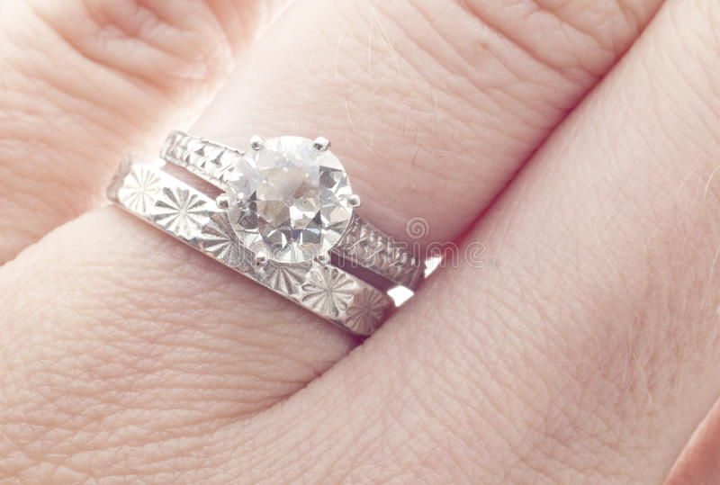 Anel e faixa antigos de casamento do diamante no dedo imagens de stock