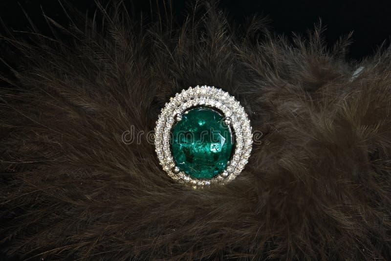 Anel esmeralda com os diamantes no fundo das penas foto de stock royalty free