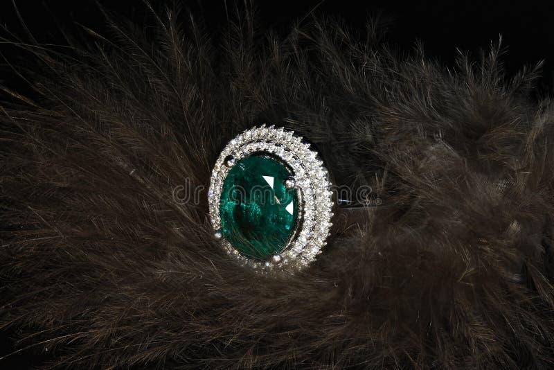 Anel esmeralda com os diamantes no fundo das penas imagens de stock
