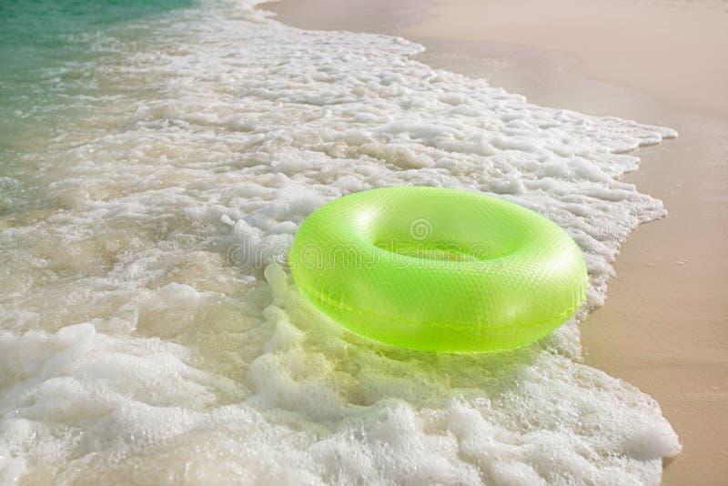 Anel flutuante na praia arenosa com ondas imagem de stock royalty free