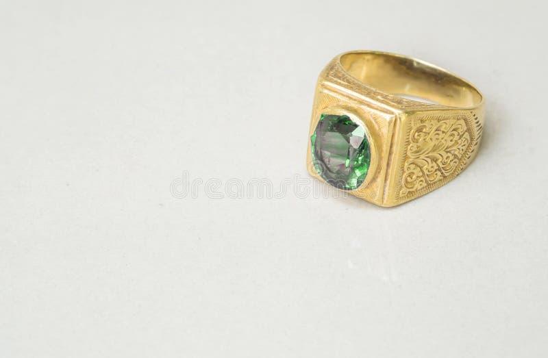 Anel verde velho do seixo do close up no fundo de pedra de mármore cinzento borrado da textura do assoalho com espaço da cópia fotos de stock