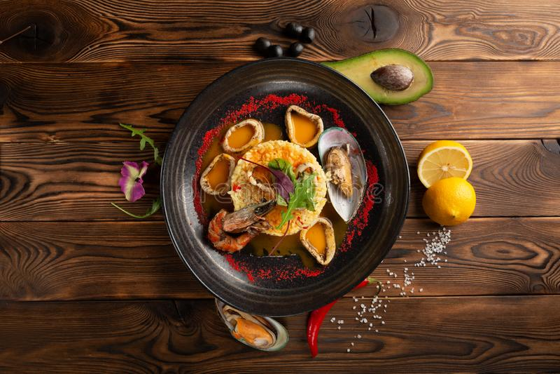 Anelli al forno del calamaro con riso e le spezie nella banda nera fotografie stock