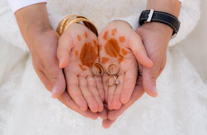 Anelli della holding dello sposo & della sposa fotografia stock