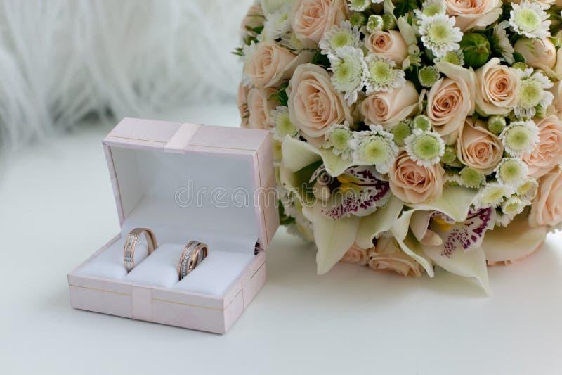 Anelli della sposa e dello sposo di nozze in una scatola sulla tavola immagini stock