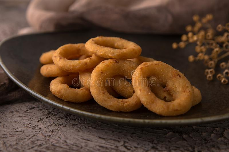 Anelli delle cipolle o del calamaro in pastella su fondo nero Spuntino a birra Spuntino a birra immagini stock
