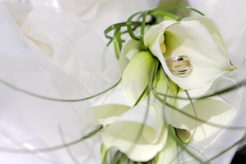Anelli di cerimonia nuziale con i fiori fotografia stock libera da diritti
