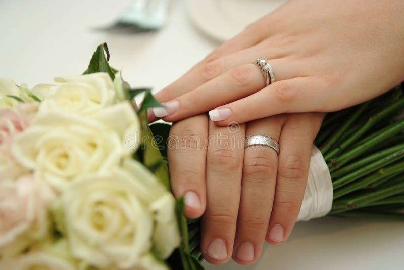 Anelli di cerimonia nuziale da portare dello sposo & della sposa fotografia stock