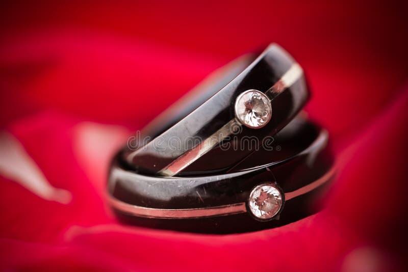 Anelli di cerimonia nuziale scuri sui petali rossi
