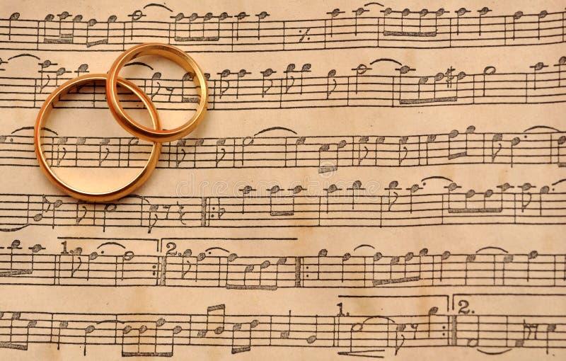 Anelli di cerimonia nuziale su musica fotografia stock libera da diritti