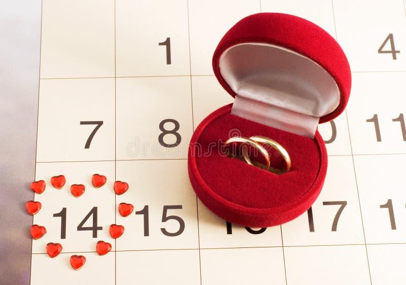 Anelli di cerimonia nuziale sul calendario, giorno del biglietto di S. Valentino fotografia stock libera da diritti