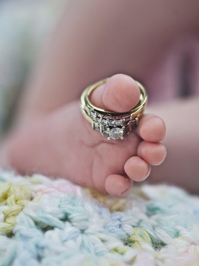 Anelli di cerimonia nuziale sul piede del bambino fotografie stock libere da diritti