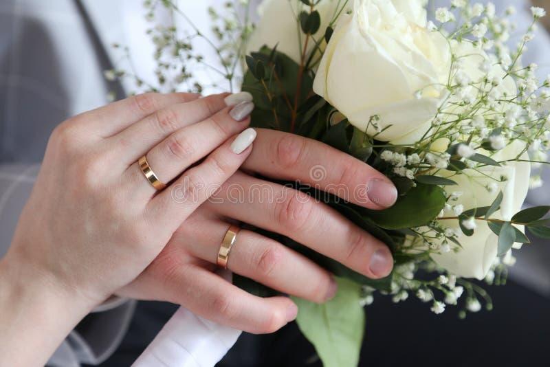 Anelli di cerimonia nuziale sulle mani fotografia stock libera da diritti