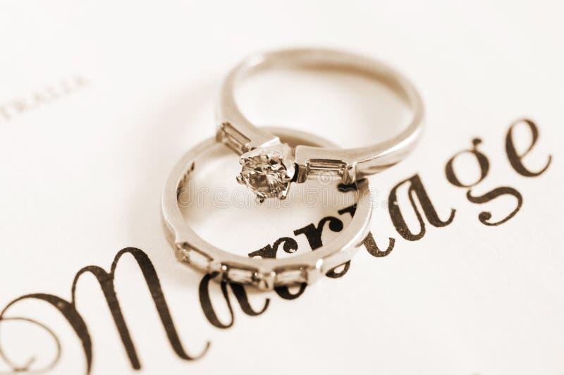 Anelli di fidanzamento d'annata di nozze e del diamante di stile di seppia retro sul certificato di matrimonio fotografia stock libera da diritti