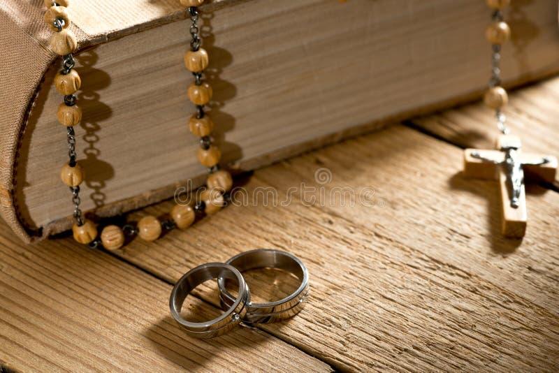 Anelli di nozze, bibbia e perle di preghiera fotografia stock