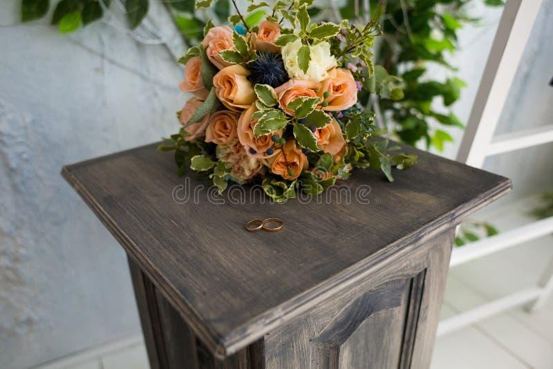 Anelli di nozze su un piedistallo di legno colorato sullo sfondo di un elegante bouquet nuziale immagini stock