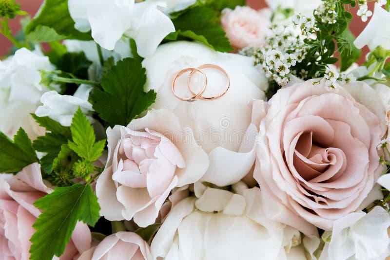 Anelli di oro di nozze su un mazzo dei fiori fotografia stock