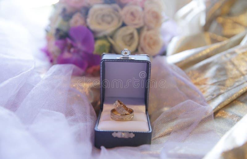 Anelli di oro di nozze in una scatola su un tessuto dorato con un velo e un mazzo dei fiori lusso fotografie stock