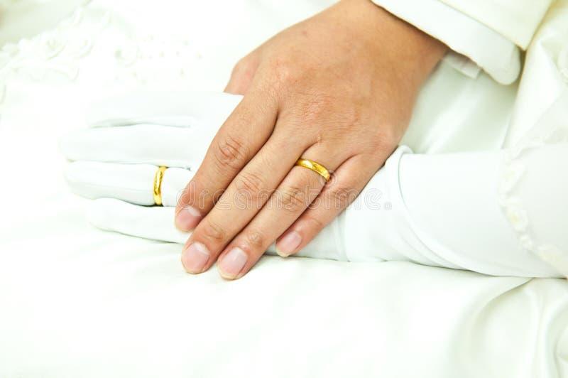 Anelli di oro sugli anulari della sposa e dello sposo fotografie stock
