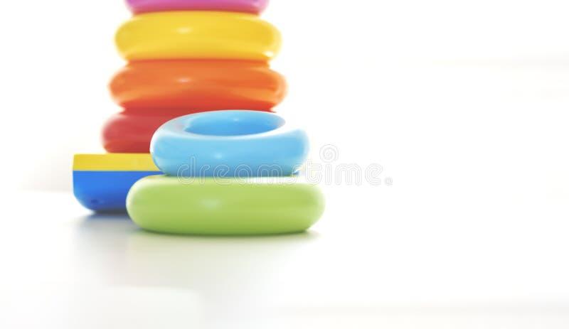 Anelli di plastica variopinti su un fondo bianco da impilare in una torre immagini stock libere da diritti