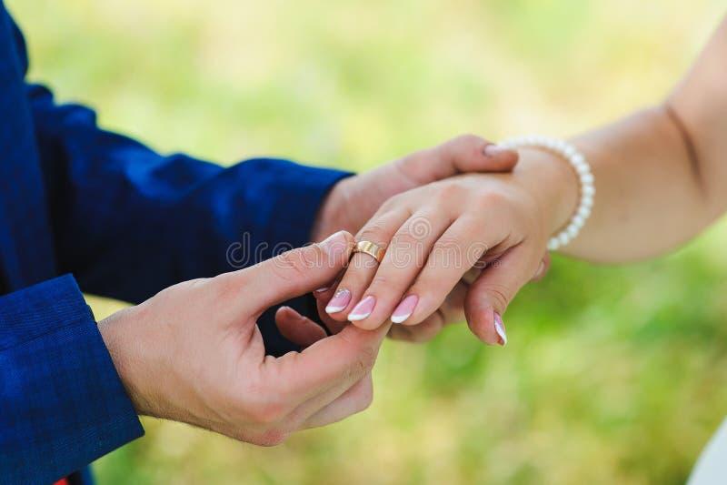 Anelli di scambio dello sposo e della sposa fotografia stock