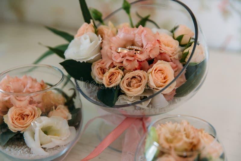 Anelli dorati di nozze decorati con i fiori su fondo bianco in grande vetro immagine stock libera da diritti