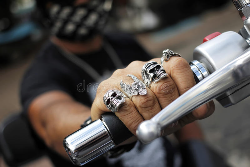 Anelli sulle dita che tengono motociclo immagine stock