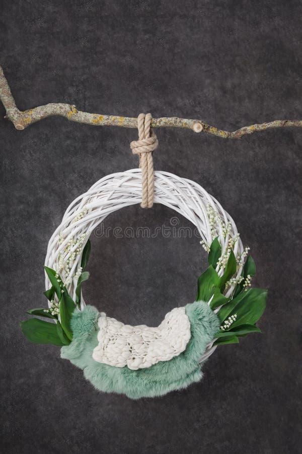 Anello bianco che appende su un bastone su un fondo grigio della grafite, modello del mughetto per un neonato immagine stock libera da diritti
