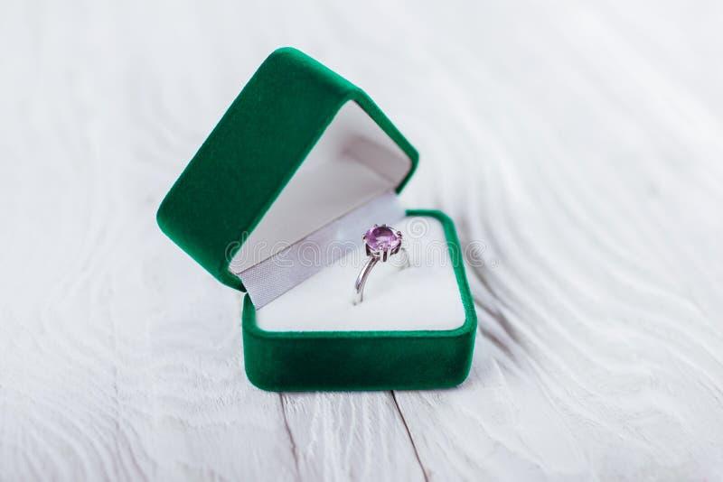 Anello d'argento con l'ametista in contenitore di regalo verde su fondo bianco Presente per il giorno dei biglietti di S immagini stock libere da diritti