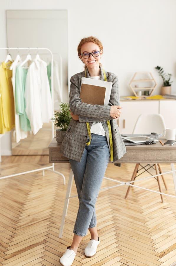 Anello da moda Dressmaker nel proprio studio, sorridendo alla telecamera immagine stock