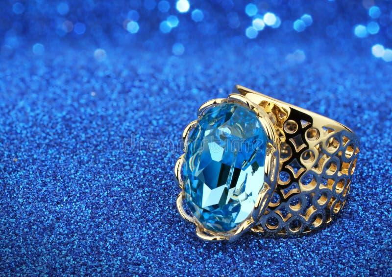 Anello dei gioielli con l'acquamarina della gemma su fondo blu fotografia stock libera da diritti