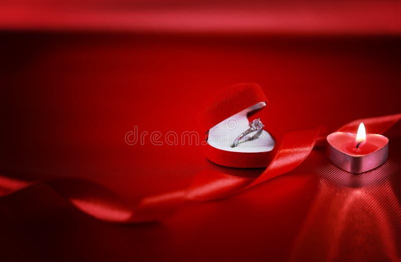 Anello del solitario di nozze in scatola rossa a forma di del cuore con la candela e nastro rosso su fondo rosso Concetto di gior fotografie stock