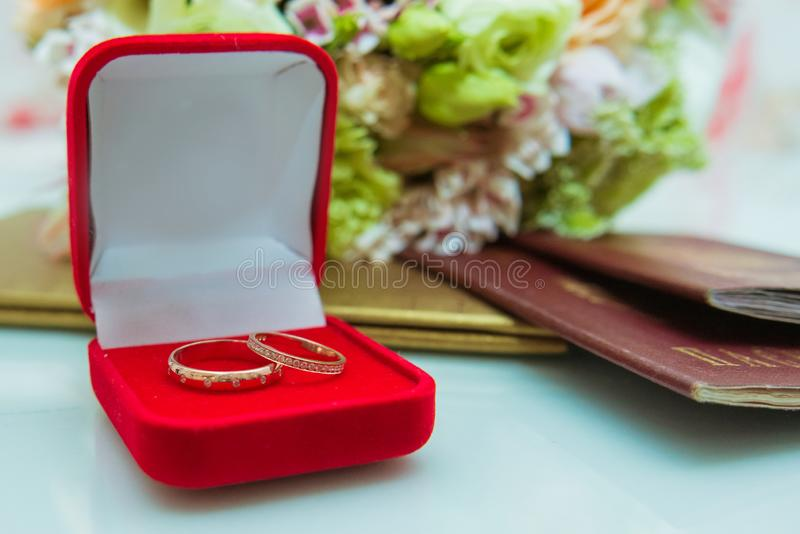 Anello di cerimonia nuziale Due anelli di diamante dell'oro della sposa e dello sposo sono sopra in una scatola rossa vicino al m fotografie stock