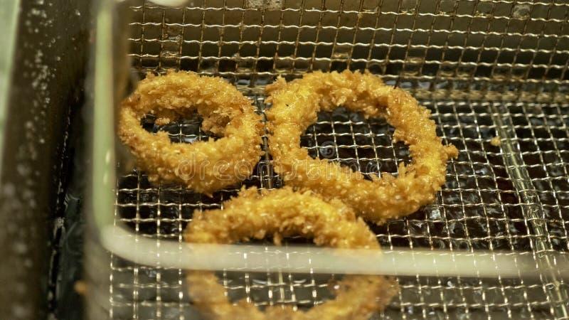 Anello di cipolla fritta Anelli di cipolla che cucinano in olio di bolle caldo in un friggitrice Cipolle dorate in cerchio friggo immagini stock libere da diritti