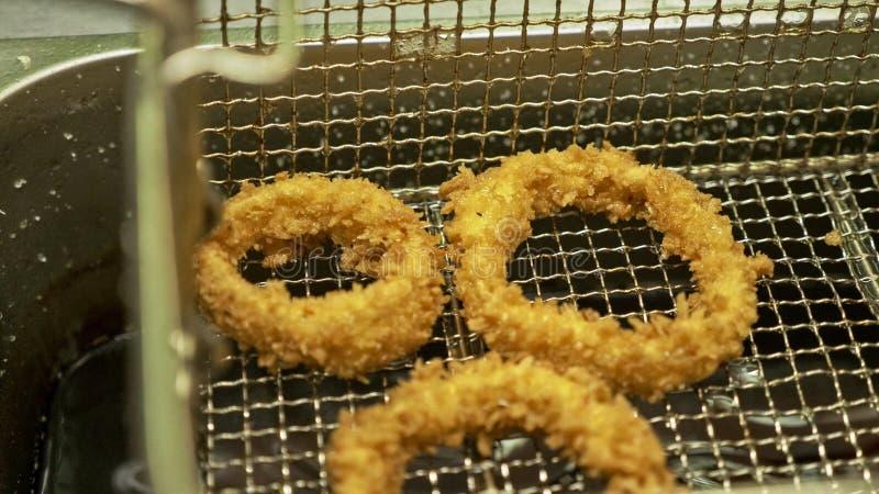 Anello di cipolla fritta Anelli di cipolla che cucinano in olio di bolle caldo in un friggitrice Cipolle dorate in cerchio friggo fotografia stock