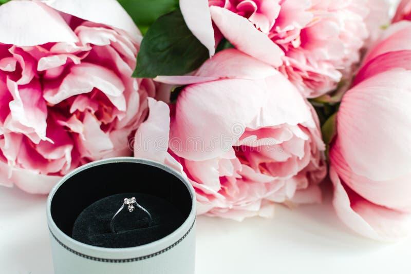Anello di diamante in una scatola, fiori rosa delle peonie su fondo bianco, spazio della copia immagini stock libere da diritti