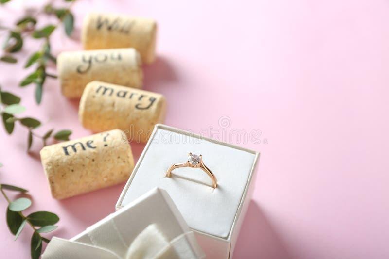 Anello di fidanzamento e testo MI SPOSERETE? sul fondo di colore fotografie stock
