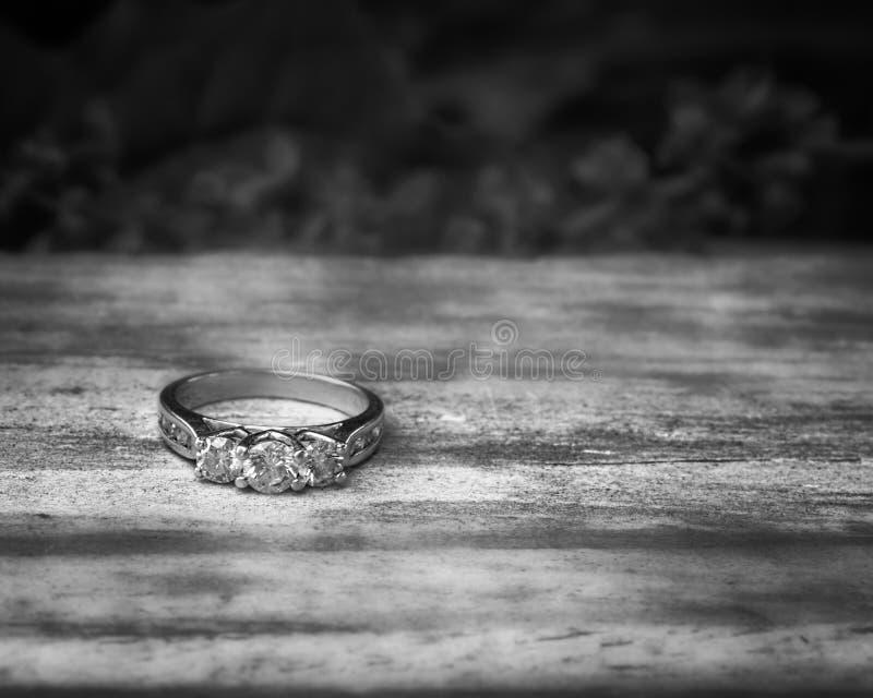 Anello di fidanzamento di pietra tre su legname immagine stock