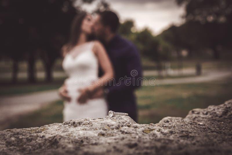 Anello di fidanzamento sulla superficie di pietra con la sposa e lo sposo vaghi nel backround fotografie stock libere da diritti
