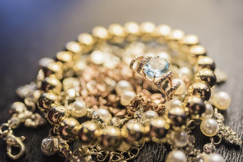 Anello di oro con il braccialetto dell'oro e del topazio sulla collana della perla fotografia stock