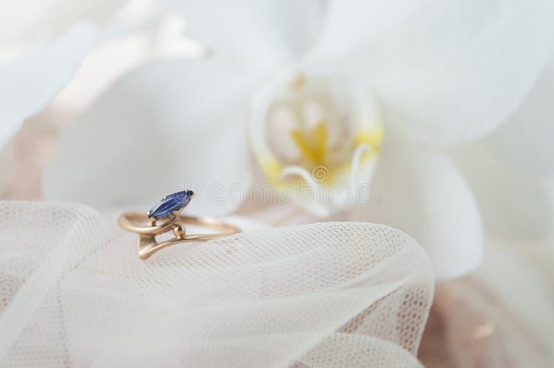 Anello di oro con una pietra blu di biossido di zirconio su un fondo bianco fotografie stock