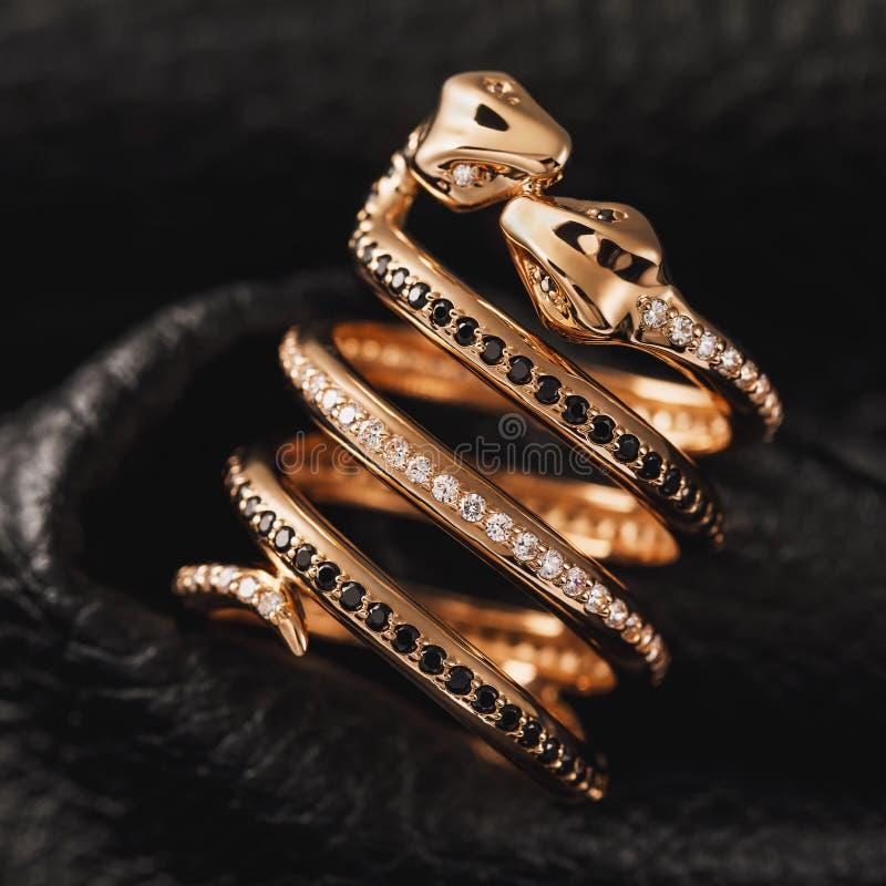 Anello di oro sotto forma di baciare i serpenti con gli zirconi ed i diamanti neri su un fondo di cuoio fotografie stock
