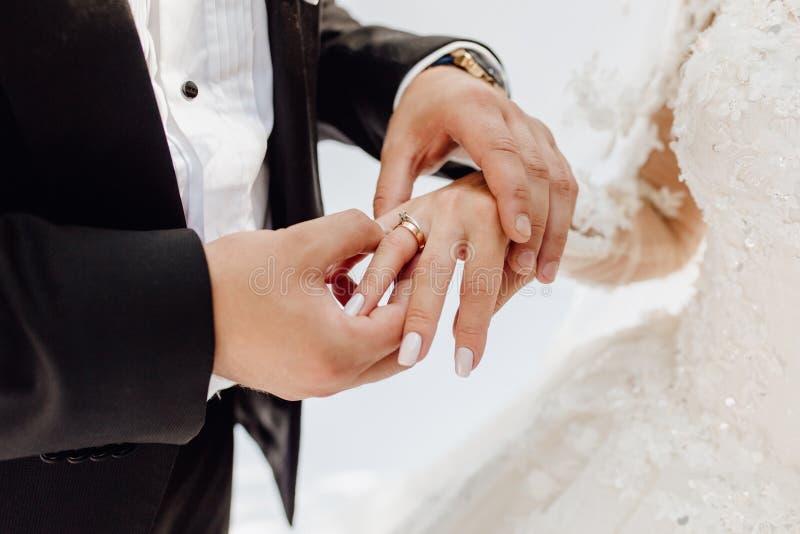 Anello di Putting Jewelry Golden dello sposo sul dito della sposa immagine stock libera da diritti