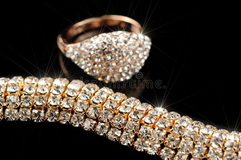 Anello e collana di oro brillanti su fondo nero immagini stock libere da diritti